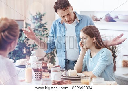 Generational misunderstanding. Loving father standing next to a young lady sitting at a table while giving a good talk to her after the daughter did something wrong.