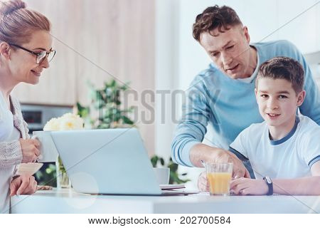 Parents are the biggest blessing. Smart youngster looking into the camera while sitting at a table and working on a school assignment with mom and dad.