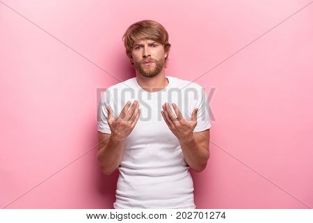 Serious businessman having no idea raised his hands on pink background. emotions, facial expressions, feelings, body language, signs concept
