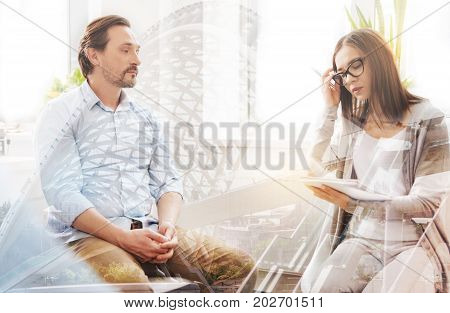 Eager to help. Young helpful professiaonl psychologist making notes and talking with a troubled man while having a psychological session