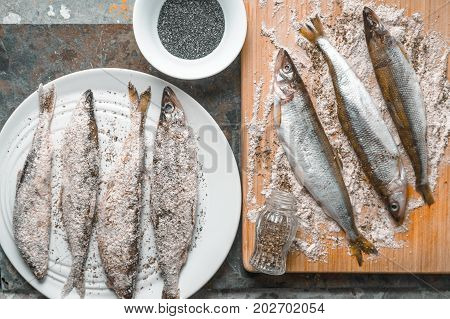 Smelt on a plate and on a cutting board, salt horizontal