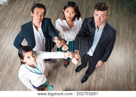 Four serious middle-aged business people standing in office hall, looking at camera and showing thumbs up. High angle view.