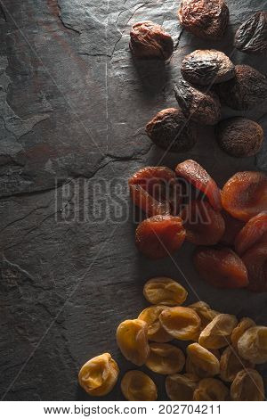Brown, orange, yellow dried apricots on a gray stone vertical