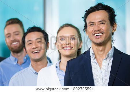 Cheerful Asian male executive leading people of his company. Excited successful business leader looking at camera, his colleagues standing behind him. Cooperation concept