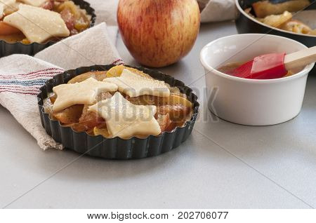 Baking process, ingredients for baking, workplace culinary, background. Ingredients (flour, egg, pie crust, cinnamon) and tools ( brush, rolling pin) to make an apple cake. Top view, copy space