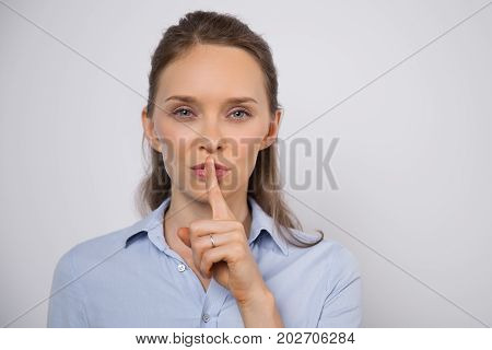 Enigmatic young businesswoman showing shh gesture and looking at camera opposite gray wall. Serious beautiful woman asking to be quiet. Secret concept