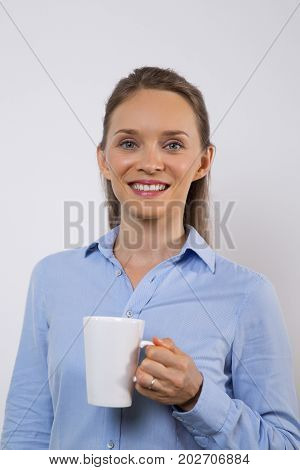Happy attractive female employee drinking coffee and looking at camera. Energetic young businesswoman with mug enjoying morning. Coffee break concept