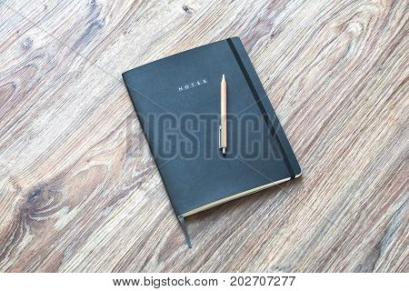 Closed classic planner with pen is on a wooden desk. Nothing extra.