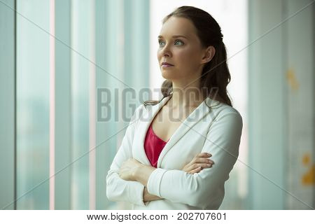 Serious smart businesswoman thinking of propensity and looking forward. Ambitious young female manager with crossed arms looking out window. Modern woman concept