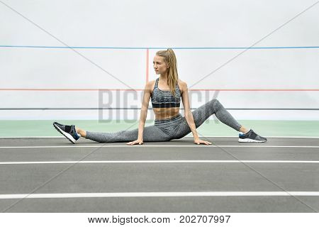 Pretty girl sits on the twine on the cycle track outdoors. She holds her hands on the ground and looks to the side. Her left leg is bent in the knee. Girl wears a gray sportswear and dark sneakers.