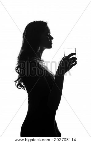 Silhouette of handsome woman with long hair with glass in her hand. She stays side to camera and looks stright. She wears a dress. Police criminal scene in black and white. Studio shot isolated or cutout from background. Studio shot.