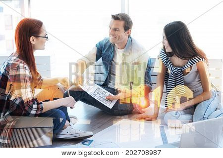 Impressive plan. Cheerful good looking colleagues having discussion about business while sitting in casual atmosphere