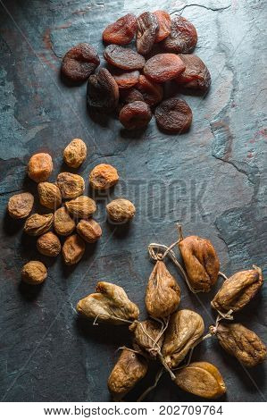 Dry figs, yellow and brown dried apricots on a gray stone vertical