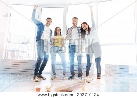 Perfect team. Cheerful enthusiastic colleagues raising hands while standing together and expressing delightful emotions