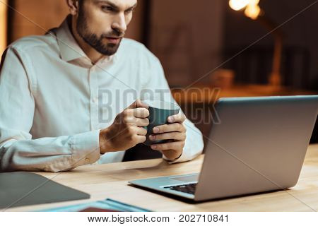 Be attentive. Serious young man sitting in semi position and holding cup with tea while putting elbows on table