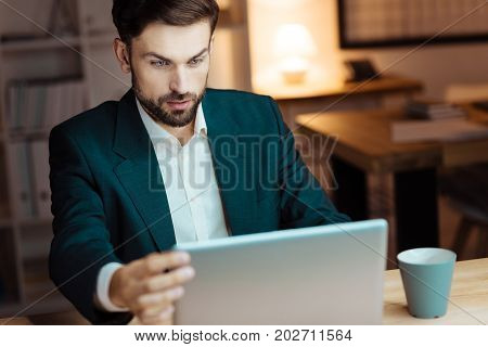 Video call. Delighted worker keeping eyes wide opened and raising eyebrows while reading new presentation