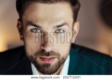 Look at me. Positive male person opening mouth and raising eyebrows while posing on camera