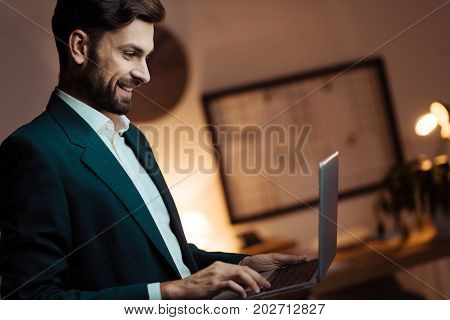 I am successful. Competent worker sitting in semi position and bowing head while looking at computer