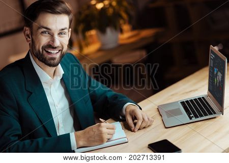 Look here. Positive man keeping smile on his face and sitting in semi position while being at his workplace