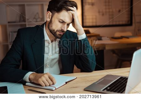 Cannot concentrate. Attentive bearded man pressing lips and touching head while putting hand on the notebook