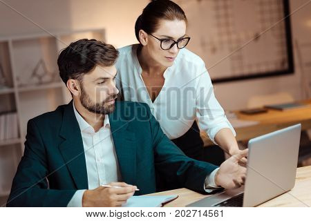 Advise me something. Handsome bearded man turning his head and actively gesticulating while looking at screen of computer