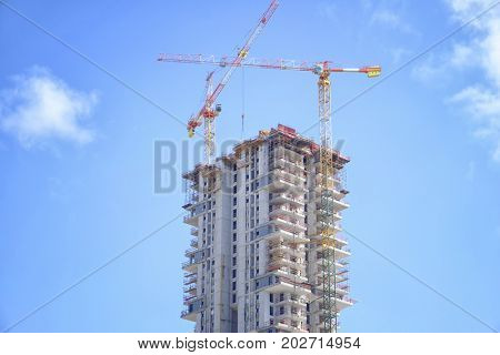Unfinished building and construction cranes with blue sky on background