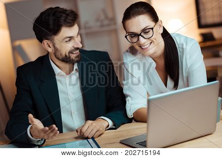 Working together. Joyful bearded man gesticulating while looking at her partner and talking to her