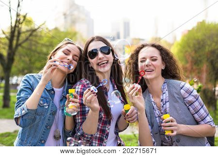 Happy teenage girls hawing fun spend time together in the city park.