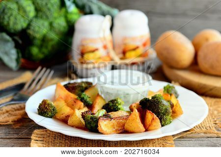 Fried potatoes slices and broccoli florets with dill sour cream sauce on a white plate. Raw potatoes slices and broccoli, pepper and salt shaker on a wooden table. Rustic style