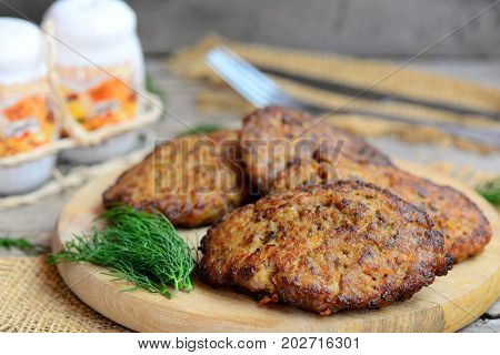 Home chicken liver pancakes with vegetables on a wood board. Fried chicken liver pancakes with carrot and onion. Cooking liver. Rustic style. Closeup