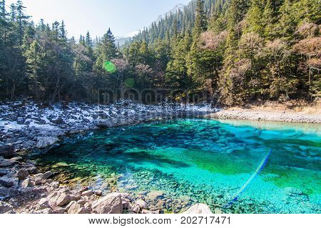 Blue round lake. Lake in the forest. The lake is in the middle of the forest. Jiuzhaigou nature reserve (Jiuzhai Valley National Park), China.