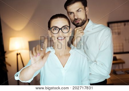 Virtual desk. Thoughtful bearded man touching his chin and raising eyebrows while standing behind his colleague