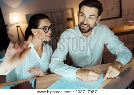 Interesting project. Handsome man keeping smile on face and raising eyebrow while making notes