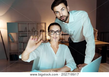 At first attention. Handsome man standing her his colleague and raising eyebrows while looking forward