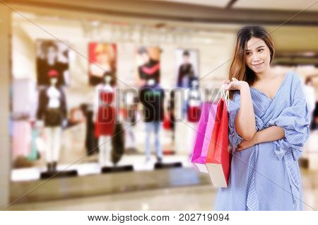 cheerful asian young woman holding shopping bags while standing at the clothing store in department store shopping mall online payment shopping online lifestyle technology concept