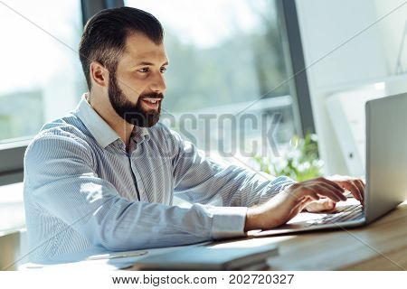 New ideas. Handsome bearded man sitting in the office and typing on the laptop, putting down his ideas, while smiling