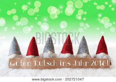 Label With German Text Guten Rutsch Ins Jahr 2017 Means Happy New Year 2018. Christmas Greeting Card With Gnomes. Sparkling Bokeh And Green Background With Snow And Stars.