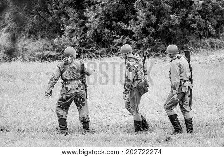 Soldiers walking with weapons.The VIII International Festival of Military History and remake for the battle