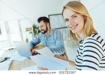 Upbeat office workers. Pleasant cheerful woman holding several printouts and smiling at the camera while her joyful male colleague sitting next to her and working on the laptop