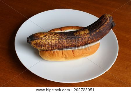 Rotten banana in a bun with mayonnaise