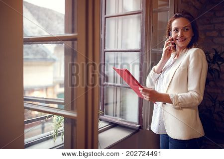 Profile of young female manager in company while talking on cell phone