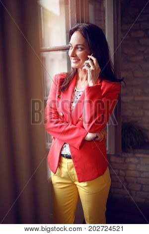 Smiling girl at job talking on cell phone
