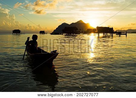 Silhouette Of Bajau Laut Young Boy Paddling A Boat During Sunrise At The Shore Of Maiga Island In Th