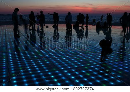 silhouettes of people in various activities at the seawall of Zadar upon sunset Croatia
