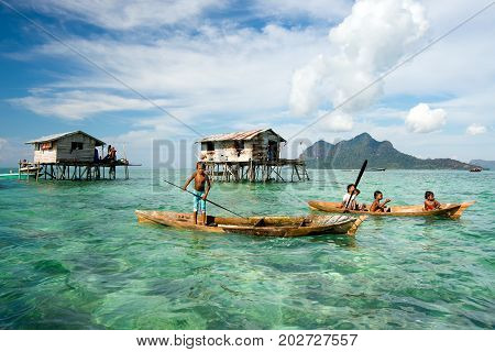 Semporna, Malaysia - 18 April, 2015: Young Bajau Laut Boy Paddling A Boat Near Stilted Houses Off Th