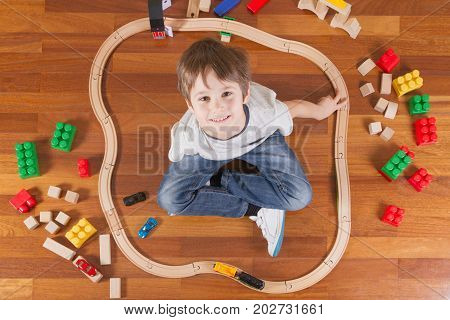 Happy child playing with toys. Boy sitting on wooden floor ant looking up at camera and smiling. Top view