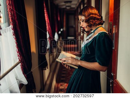 Young woman travels, vintage train compartment