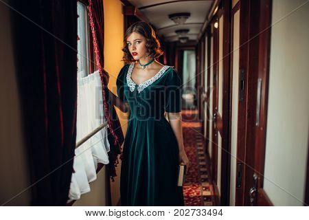 Woman in retro dress, vintage train compartment