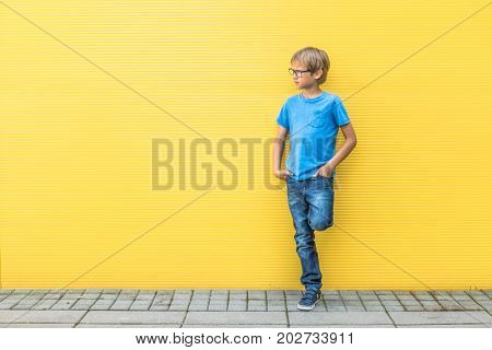 Boy with glasses standing near yellow wall oudoors.