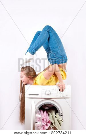 Beautiful slender girl and washing machine on white background. Advertisement of household appliances